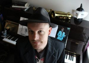 Adam Rudegeair in front of his piano