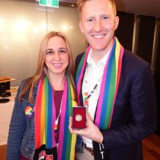 Jill Stark and Jason Ball with the coin Ball tossed to kick off the inaugural AFL Pride Game.