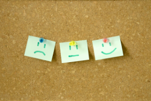 A corkboard with three cards pinned to it which each have a eyes and mouths drawn on them. The first card on the left has a sad face, the second a straight line mouth and the third has a happy face