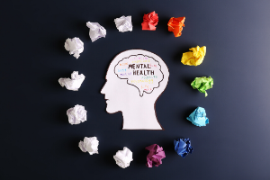 Picture of a cardboard silhouette of a head with the words 'mental health' inside a drawn-on brain. The head is surrounded by scrunched up balls of paper: some are different colours of the rainbow and some are white.