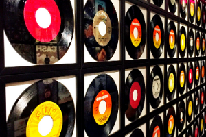 A wall with a black grid on it. In each space in the grid, a vinyl record is displayed.