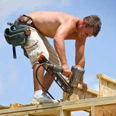 Builder using a pneumatic air nailer to secure a floor truss joist to a wall section against a blue sky. Focus on the nail gun.