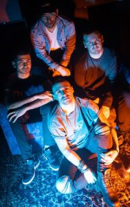The four men who are members of The Engagement sit on the ground looking up at the camera which is above them