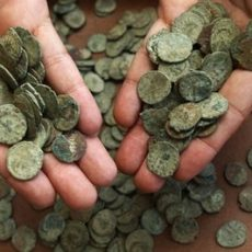 A staff member displays handfuls of coins of Tetricus I (AD271-4 ) on display at the British Museum in London, Thursday, July 8, 2010. About 52,500 Roman coins were found in a large pot by a British treasure hunter Dave Crisp using a metal detector in a field in southwest England, one of the largest treasure hoards ever found in Britain. Crisp found the coins dating from the third century AD, and is valued at 3.3 million pounds ($5 million), includes hundreds of coins bearing the image of Marcus Aurelius Carausius, the Roman naval officer who seized power in 286 and proclaimed himself emperor of Britain and northern France, ruling until he was assassinated in 293. (AP Photo/Sang Tan)
