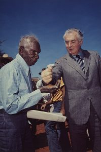 Prime Minister Gough Whitlam pours soil into hand of traditional landowner Vincent Lingiari